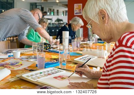 Woman in striped red and white shirt working on watercolor painting at table with other students in spacious studio