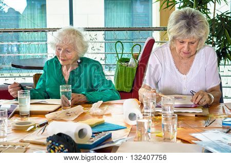 Two adorable senior women painting at table crowded with art supplies in spacious room