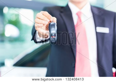 Car dealer handing over auto key