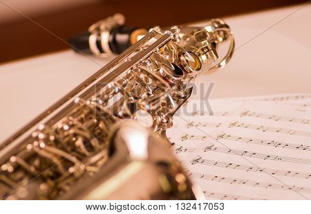 Closeup partly view of shiny saxophone lying on musical notes paper.