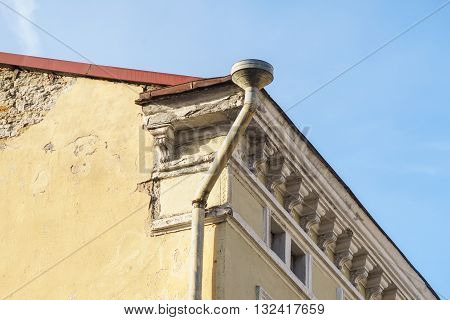 Rain gutter and downspout on corner of old style house