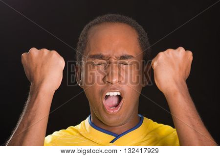 Headshot dark skinned male wearing yellow football shirt in front of black background, eyes closed and mouth open cheering with arms raised.