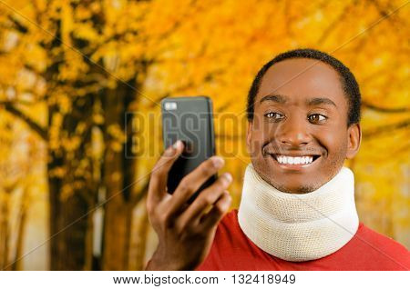 Injured young positive black hispanic male wearing neck brace and smiling, holding up cell phone as in taking selfie, yellow abstract background.