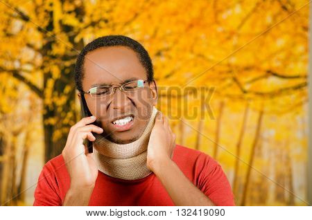 Injured young positive black hispanic male wearing neck brace, talking on phone and hand holding support in agony, yellow abstract background.