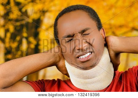 Injured black hispanic male wearing neck brace, holding hands in pain around support making faces of agony, yellow abstract background.