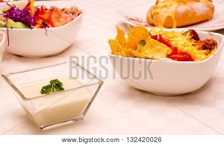 Selection of different delicious dishes sitting on white table, philly sandwich, tortilla salad.