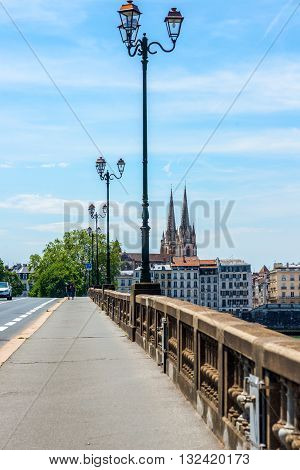 Bayonne France - May 21 2016: Pont Saint-Esprit bridge over the Adour river connects the Saint-Esprit district to Gran Bayonne and the Cathedral of Sainte-Marie de Bayonne in background. France.