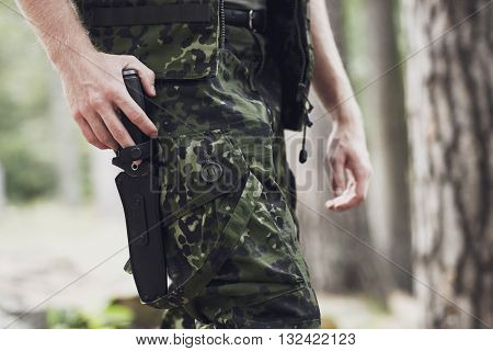 war, army, cold steel arms and people concept - close up of young soldier, ranger or hunter holding hand on knife walking in forest