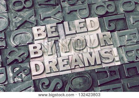 be led by your dreams exclamation made from metallic letterpress blocks with dark letters background