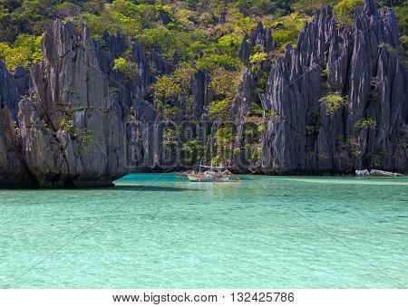 Landscape with filippino boat, rocks and blue bay. El Nido,  Palawan island, Philippines