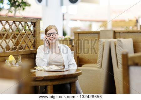 Portrait of a beautiful woman in a cafe. Blonde 40-45 years