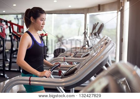 sport woman young person running on treadmill in fitness gym center