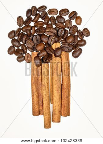 Heap of coffee beans and row of cinnamon sticks in shape of bouquet
