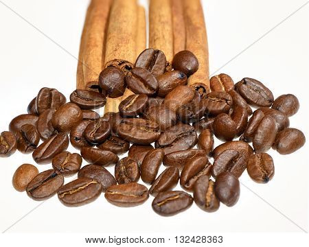 Coffee beans heap in front of few cinnamon sticks against white background