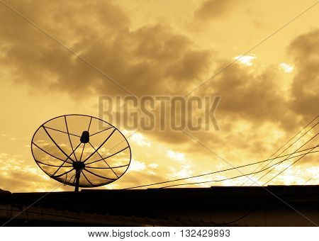 Silhouette Satellite dish with sunset sky this image focus main on satellite and have right empty space for input text.