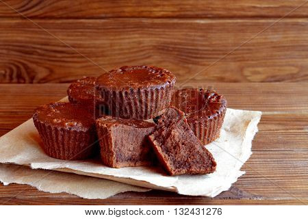 Chocolate cupcakes recipe. Sweet delicious cupcakes made from butter, cocoa, chocolate, sugar, flour, eggs. Oven baked muffins. A lot of chocolate cupcakes on paper and wooden table. Close-up
