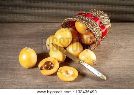 loquats in basket on wooden background. Vintage style