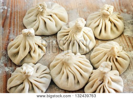 Chinese dumplings uncooked on wooden background. Street food booth selling Chinese specialty Steamed Dumplings. Process of cooking dumplings.