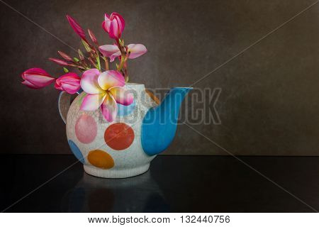 Beautiful Pink Yellow And White Flower Plumeria Or Frangipani In Fancy Baked Clay Teapot On Still Li