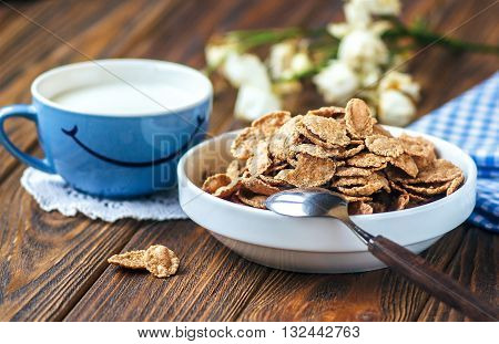 Cereal in white ceramic bowl with spoon on wooden table. Multigrain flakes and cup of milk with smile. Good morning or Have a nice day message concept. Healthy breakfast and diet concept, close up.