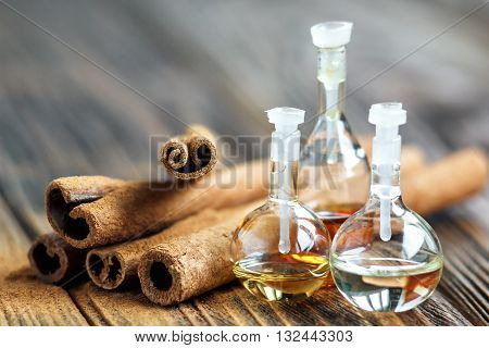 Essential oil in glass bottle with cinnamon sticks-beauty treatment. Spa concept. Selective focus.