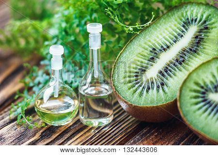 Essential oil in glass bottle with fresh, juicy kiwi fruit and green leaves-beauty treatment. Spa concept. Selective focus.