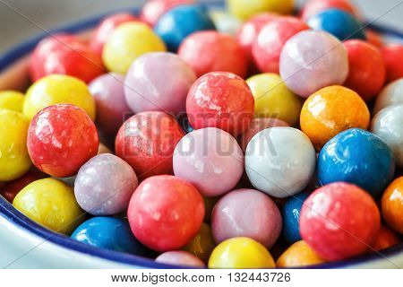 Colorful candies in jar on table in shop, closeup.