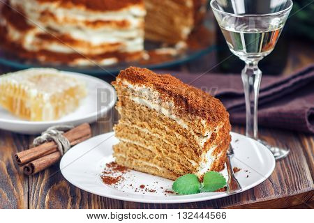 Slice of homemade layered honey cake with honeycomb, mint and cinnamon, traditional food of Jewish New Near. Sweet food