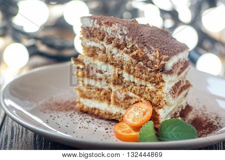 Slice of homemade layered honey cake with mint, kumquat and walnuts, traditional food of Jewish New Near. Sweet food
