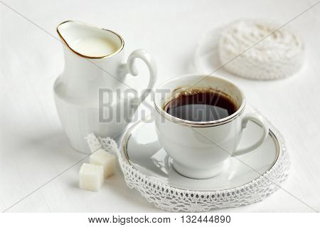 Coffee cup and saucer with milk and sugar on white background