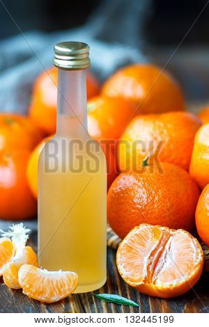 Fresh juice of ripe mandarins or tangerine liquor in a small bottle, selective focus