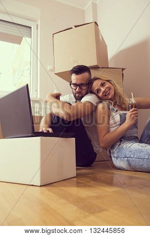 Young couple in love sitting on the floor of their new appartment planning redecoration and drinking juice