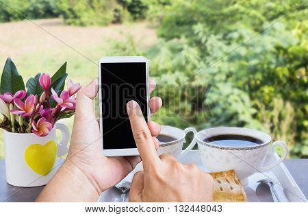 Hand Press On Big Blank Smartphone Screen Or Mobile Phone On Coffee Table And Nature View Background