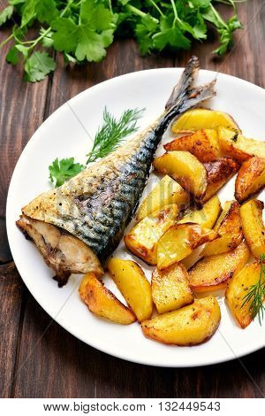 Baked potato wedges and mackerel fish on plate
