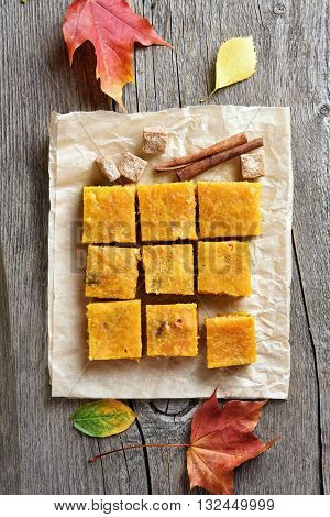 Pumpkin squares over baking paper on wooden background top view