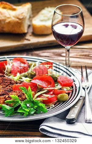 Homemade Breaded German Weiner Schnitzel and fresh vegetable spring salad with tomato, green olives, cabbage and parsley in white bowl on wooden table, closeup.