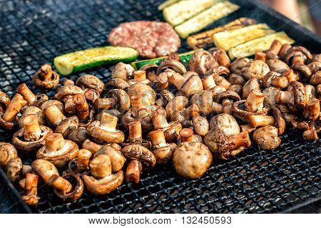 Champignon white mushrooms grilled on grill or BBQ steam and small drops of water. Cooking mushrooms on the grill. Portobello mushrooms marinated and grilling. Grilled vegetables on a grill close up.