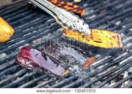 Vegetarian barbecue with eggplant seasoned with olive oil, garlic and herbs. Grilled vegetables preparing on a barbecue grill over charcoal. Aubergine or eggplant, sliced and grilled on bbq.