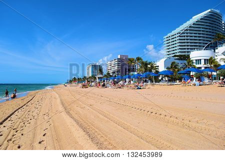May 22, 2016 in Ft Lauderdale, FL:  People relaxing and sunbathing on the sandy Ft Lauderdale Beach with lounge chairs and umbrellas on the Atlantic Ocean surrounded by modern highrise buildings where locals and tourists can spend leisure time taken in Ft