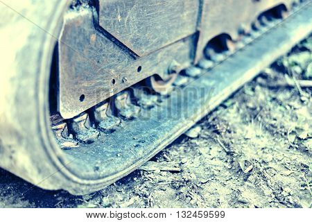 Bulldozer or earth mover with selective focus and copy space. Heavy machine on a construction site. Close-up or macro shot of a caterpillar track.