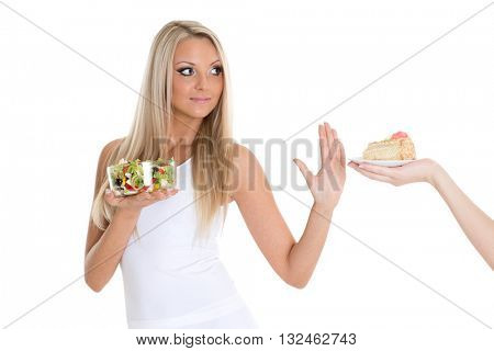 Young beautiful woman choosing between bowl of salad with fresh vegetables and piece of cake on a white background.  Concept of healthy food.