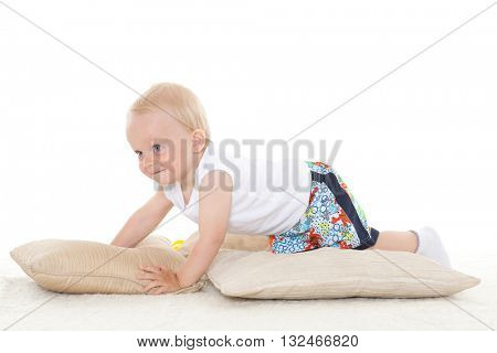 Sweet small baby is playing with pillows on a white background.