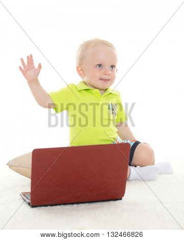 Sweet yearling baby boy  with laptop sits on the floor on a white background.