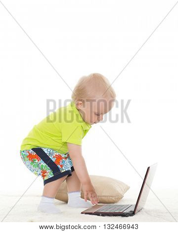 Sweet yearling baby boy  with laptop stands on a white background.