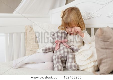 Sad pretty girl with toy bear sits on a sofa in the room.