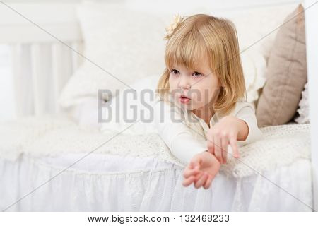 Resentful pretty little girl lies on a sofa in the room.
