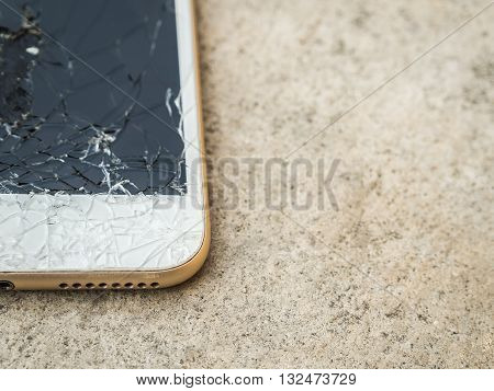 Close up of broken mobile phone or tablet droped on cement floor with copy space High key