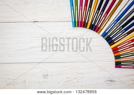 colored pencils on white boards flat lay