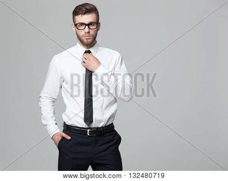 Studio Shot Of Young Handsome Businessman On Gray Background.