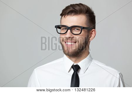 Studio Portrait Of Handsome Young Businessman Smiling And Winking.
